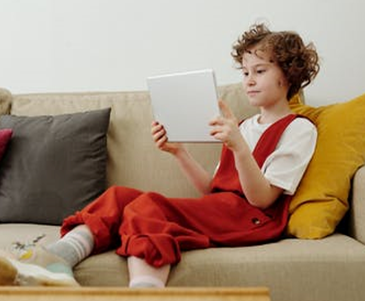 Child using a tablet, seated on a couch.