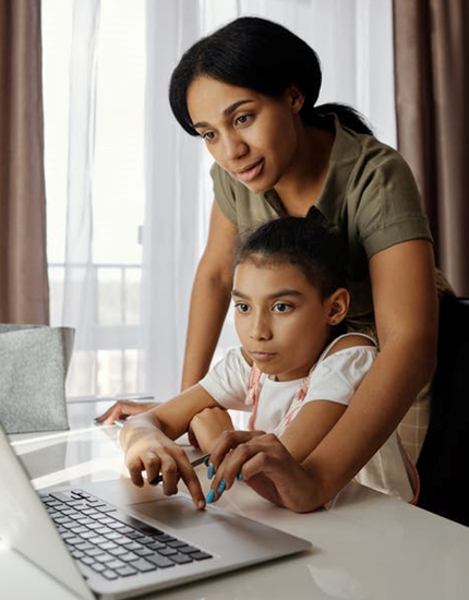 Adult and child using a laptop at a table.